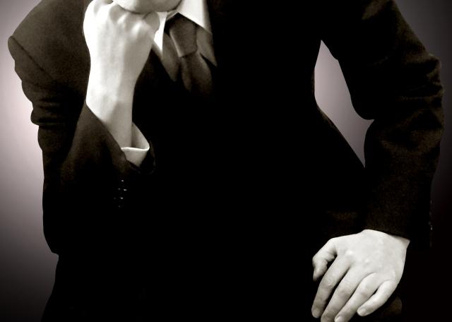 腕を顎にあてて悩むスーツの男性