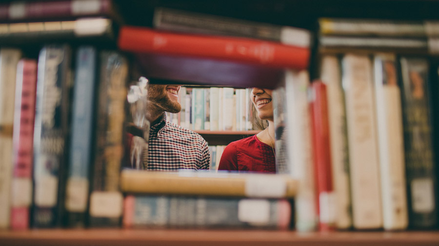 図書館の本の隙間から見えるカップル
