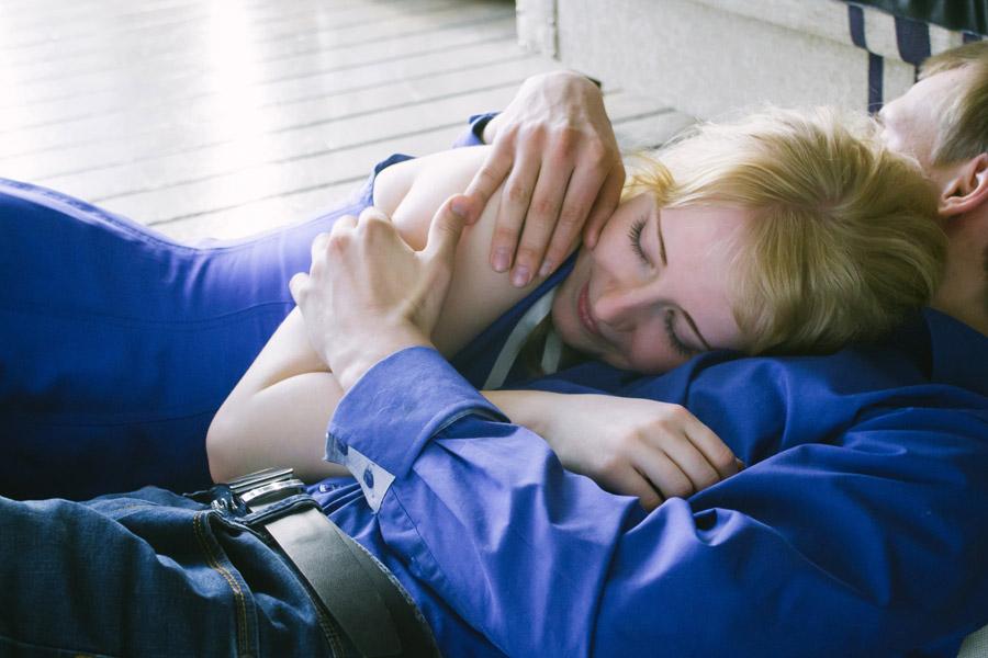 床の上で女性を抱きしめる男性