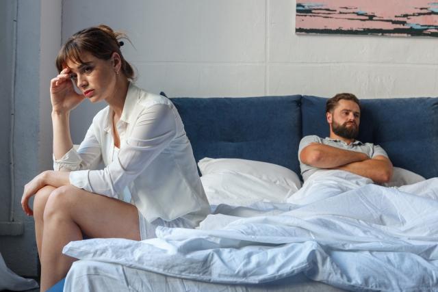 ベッドの上で喧嘩する夫婦