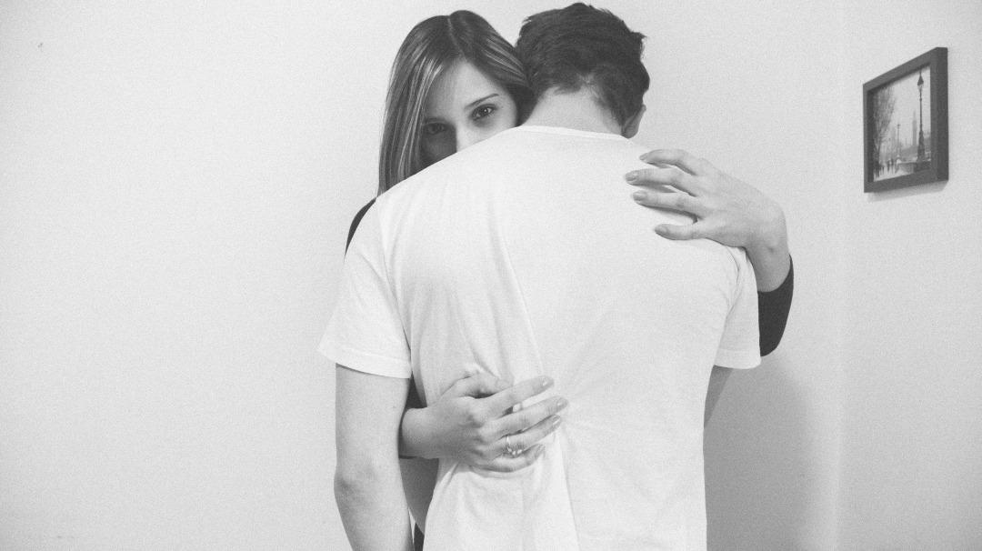 落ち込む男性を抱きしめる女性