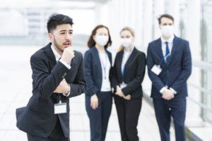 咳き込む同僚を見つめる会社員