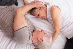 ベッドに寝転ぶ不倫シニアカップル